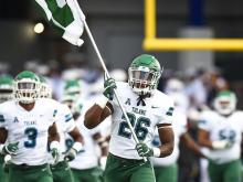Tulane football players run onto the field