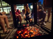 Students gathered around a campfire, toasting marshmallows