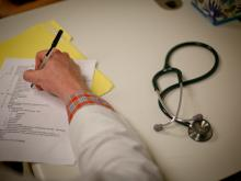 A hand is holding a pen and filling out a form. A stethoscope sits to the right