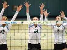 Three women's volleyball players stand at the net with arms outstretched, watching for the ball